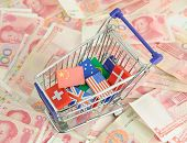 shopping cart with national flag on a lot of Renminbi on white background poster