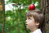 stock photo of bow arrow  - kid with apple on his head and arrow shot through - JPG