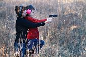 stock photo of handgun  - Mother teaching her young daughter how to safely and correctly use a handgun - JPG