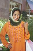 stock photo of dupatta  - Portrait of a happy middle aged Indian female with shopping bags - JPG
