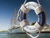stock photo of historical ship  - wiew on the sailing ship thru blue safe belt with welcome on board sign - JPG