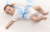 image of bodysuit  - Infant baby boy in white bodysuit and blue ribbon - JPG