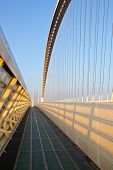 picture of calatrava  - Reggio Emilia bridge by Calatrava detail showing curved hoop design and suspension wires with pedestrian sidewalk second bridge beyond against blue sky at sunset Emilia Romagna Italy - JPG