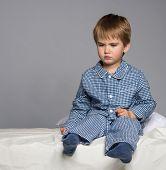 stock photo of pyjama  - Disappointed little boy in blue pyjamas on bed - JPG