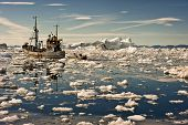 stock photo of ice fishing  - Fishing boat going through the icy waters at the sunset of Ilulissat - JPG