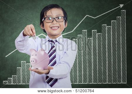 Little Boy Puts The Coin Into The Piggy Bank