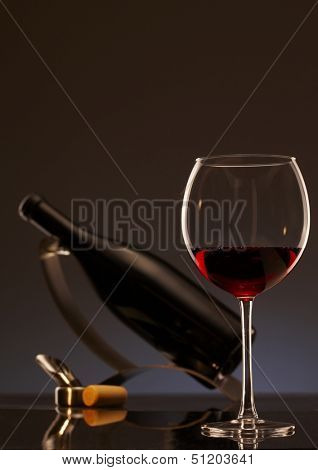 Elegant photo of a glass of red wine with bottle in background.