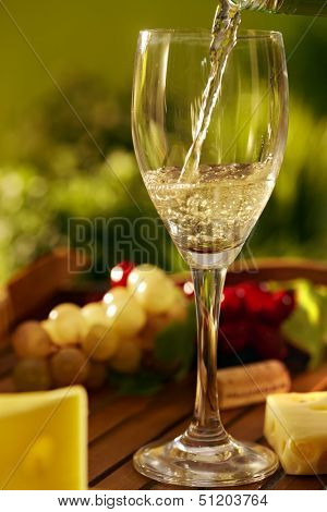 Outdoor still life photo of a glass of white wine and cheese on a wooden tray,