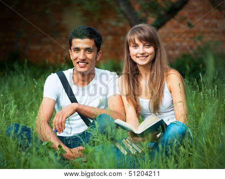 Two Students In Park On Grass With Book Outdoors