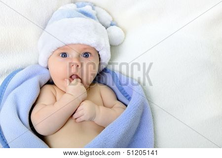 christmas cute baby boy, beautiful infant in Santa's hat and blue soft plaid with vivid positive expression