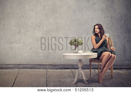 beautiful woman sitting in a living room drinking tea