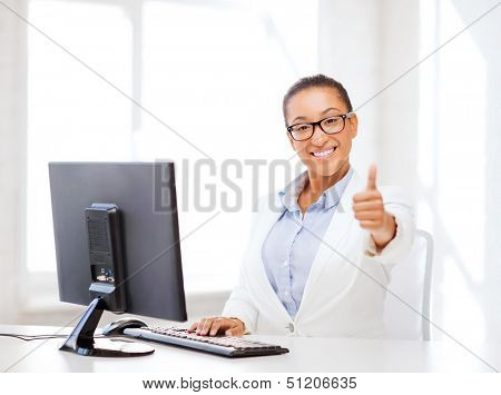 business and internet concept - smiling african businesswoman with computer in office showing thumbs up