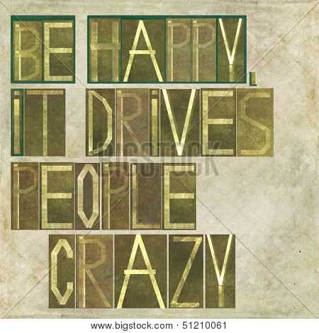 """Earthy background image and design element depicting the words """"Be happy, it drives people crazy"""""""