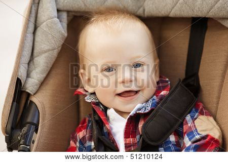 Beautiful little smiling baby in a baby carriage on the streets of the city. Smile of  a child sitting in a pram. A child laughs