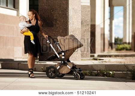 Trendy modern mother on a city street with a pram. Young mother walks with a child in  the city. Beautiful young woman with a child in a baby carriage