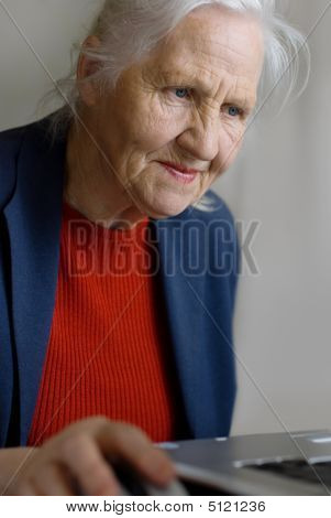 Old Woman Typing On Laptop
