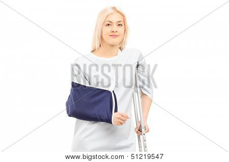 Blond female patient in hospital gown with broken arm and crutch isolated on white background