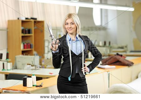 Female owner of a small business standing inside a textile factory holding a scissors in her hand