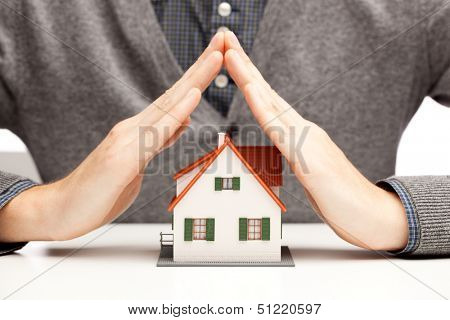 Hands as a protecting roof over a little house over white