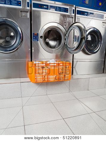 Basket of clothes kept in front of open washing machine at laundromat