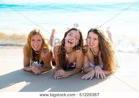happy three friends teen girls lying on beach sand smiling