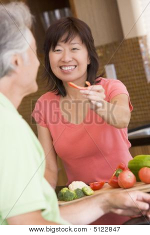 Woman Offering Husband A Piece Of Freshly Chopped Pepper