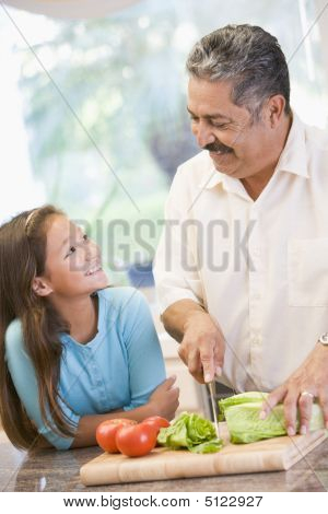 Grandfather And Granddaughter Preparing Meal, Mealtime Together