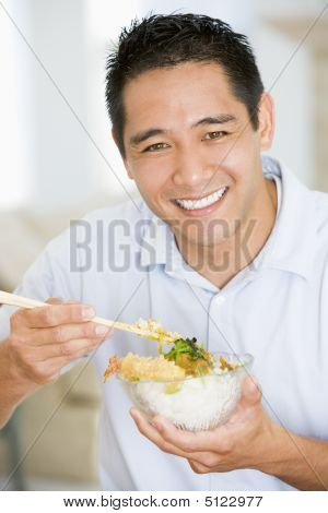 Man Enjoying Chinese Food With Chopsticks