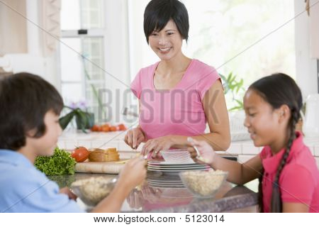 Children Enjoying Breakfast While Mother Is Preparing Food