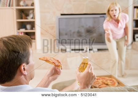 Wife Telling Husband Off For Drinking Beer And Eating Pizza