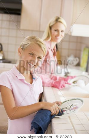 Mother And Daughter Cleaning Dishes