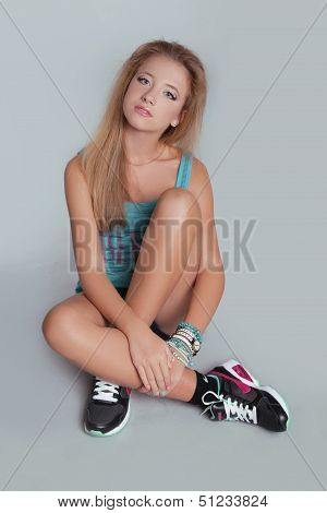 Young Teen Girl Sitting With Sporty Sneakers Shoes. Studio Photo