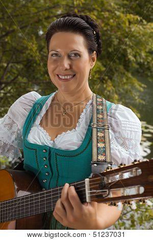 Bavarian woman in dirndl smiling while playing guitar at the lake
