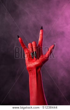 Rock sign, red devil hand with black nails, Halloween