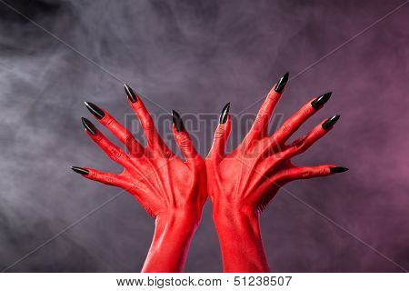 Red devil hands with sharp black nails, extreme body-art, studio shot over smoky background