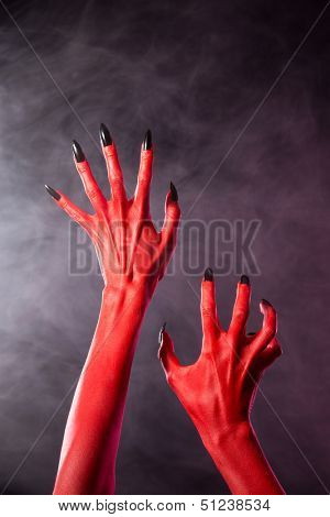 Red devil hands with black nails, Halloween theme, studio shot over smoky background