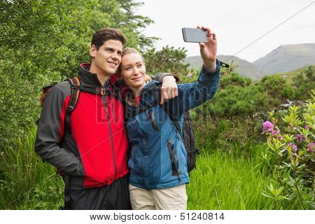 Happy couple on a hike taking a selfie in the countryside