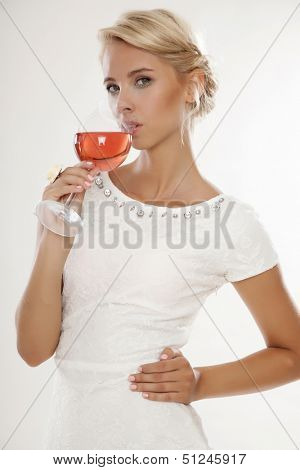 Portrait of happy smiling young attractive blonde woman with glass of red rose wine, in white dress isolated on white background