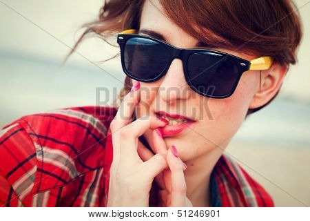 Portrait of a pretty fashionable, young woman in a chequered red shirt and sunglasses on the beach