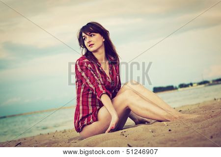 Pretty fashionable young woman in a chequered red shirt relaxing on the beach
