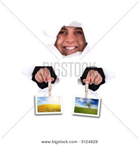 Young Woman Holding Landscape Photos Thru Wall Hole