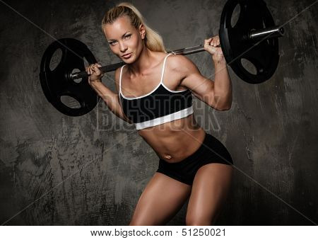 Beautiful muscular bodybuilder doing exercise with weights
