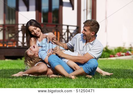 Family with a child playing on a lawn