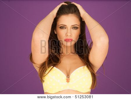 Cropped studio portrait of a beautiful sexy seductive woman with a deep cleavage posing in a bra with her arms folded looking at the camera against a purple background