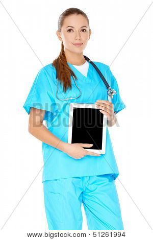 Attractive serious young female doctor or nurse in green scrubs with a tablet-pc or notebook displayed in her hands  screen visible to viewer