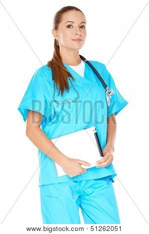 Attractive serious young female doctor or nurse in green scrubs with a tablet-pc or notebook displayed in her hands