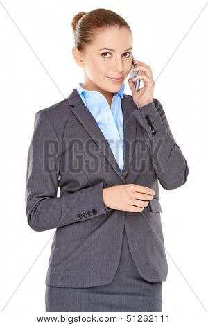 Stylish young businesswoman on her mobile phone standing listening to the conversation with a feint smile