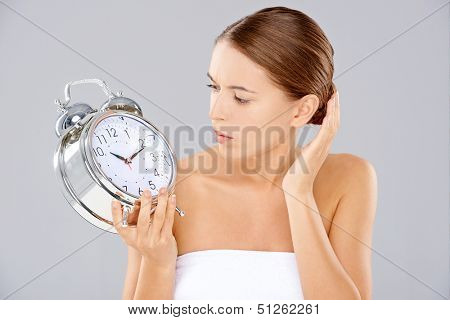 Beautiful young woman looking at a large silver retro alarm clock with bells that she is holding in consternation as though waiting for it to ring