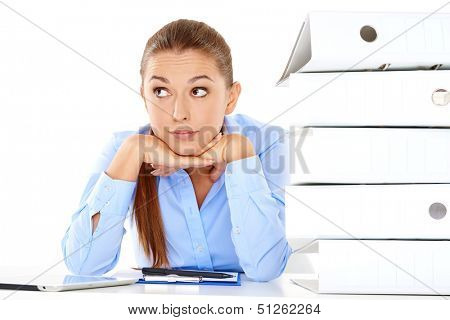 Overworked stressed young businesswoman staring at the camera with her head on her hands alongside a tall stack of office files with paperwork