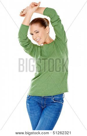 Sexy stylish young woman in a green jersey posing with her hands on her hips giving the camera a playful flirtatious smile